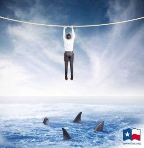 man hanging over sea of sharks