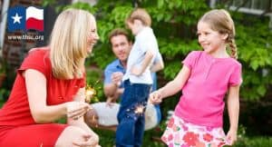Mom teaches girl to hold sparklers, father, son in background