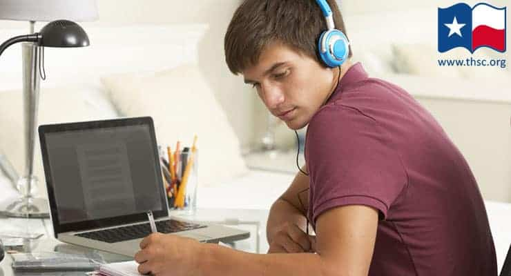 Teen boy studying at desk with headphones on